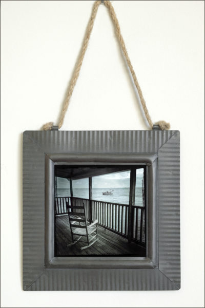 fine art print on metal with tin frame of a wooden rocking chair on porch watching shrimp boat on the ocean at sea, moody nostalgic