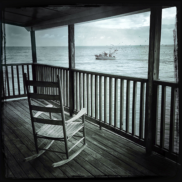 fine art print of rocking chair on porch with shrimp boat on the sea ocean